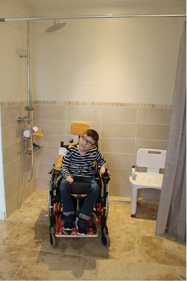 Lucas pose fièrement dans sa nouvelle salle de bains aux normes handicapées